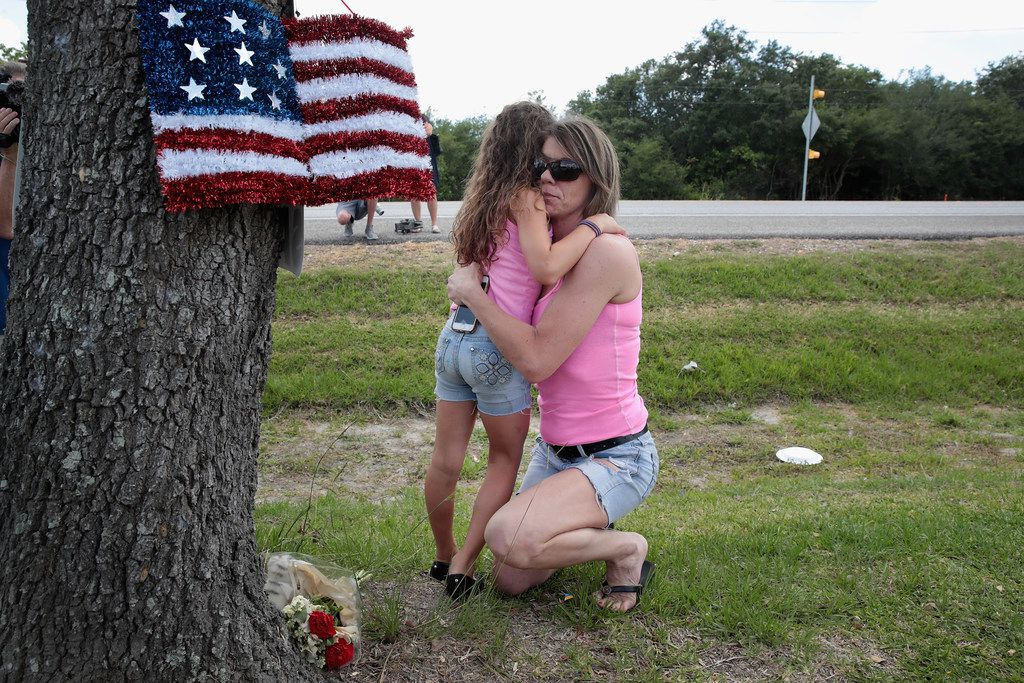 Carissa Potts hugs her 7-year-old daughter, Kaylee, after leaving flowers at a small memorial outside of  Santa Fe High School on May 19 in Santa Fe, Texas, a day after a mass shooting at the school.