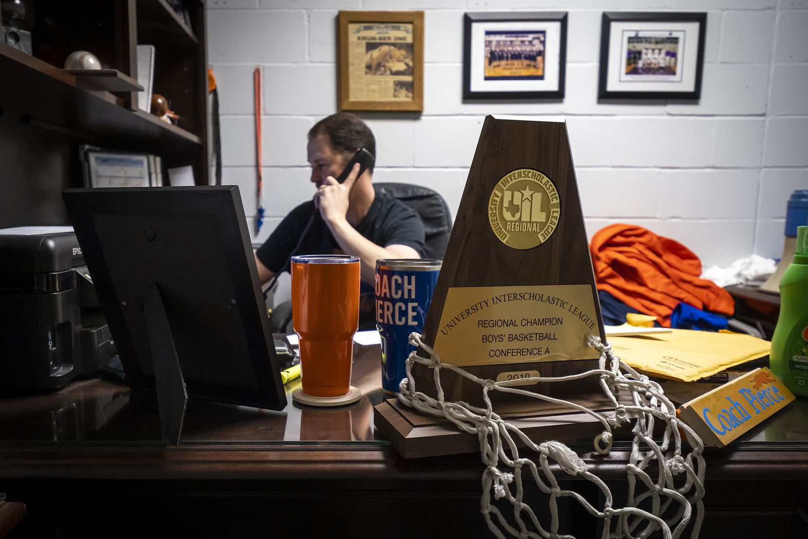 The team's 2019 UIL Regional Championship trophy sit on his desk as Slidell High School head coach Casey Pierce's makes a phone call in his office after practice at the school on Tuesday, March 5, 2019, in Slidell, Texas. Slidell High School, northwest of Denton, is trying to win its first state boys basketball title since 1943. (Smiley N. Pool/The Dallas Morning News)