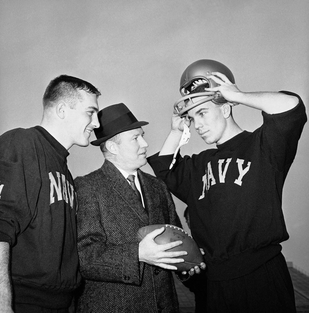 Navy coach Wayne Hardin (center) talks with his star quarterback, Roger Staubach (right), in final workout in Philadelphia Stadium on Dec. 7, 1963, before annual battle against Army, with center Tom Lynch listening in.