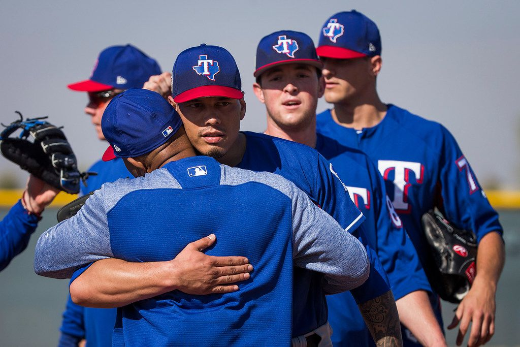 Texas Rangers pitcher Keone Kela (facing) hugs third base coach Tony Beasley during a spring training workout at the team's training facility on Sunday, Feb. 18, 2018, in Surprise, Ariz. (Smiley N. Pool/The Dallas Morning News)