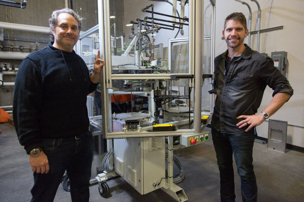 Chief Creative Officer Dustin Blocker (right) and Chief Operations Officer Alex Cushing (left) stand near a record press machine at Hand Drawn Pressing.