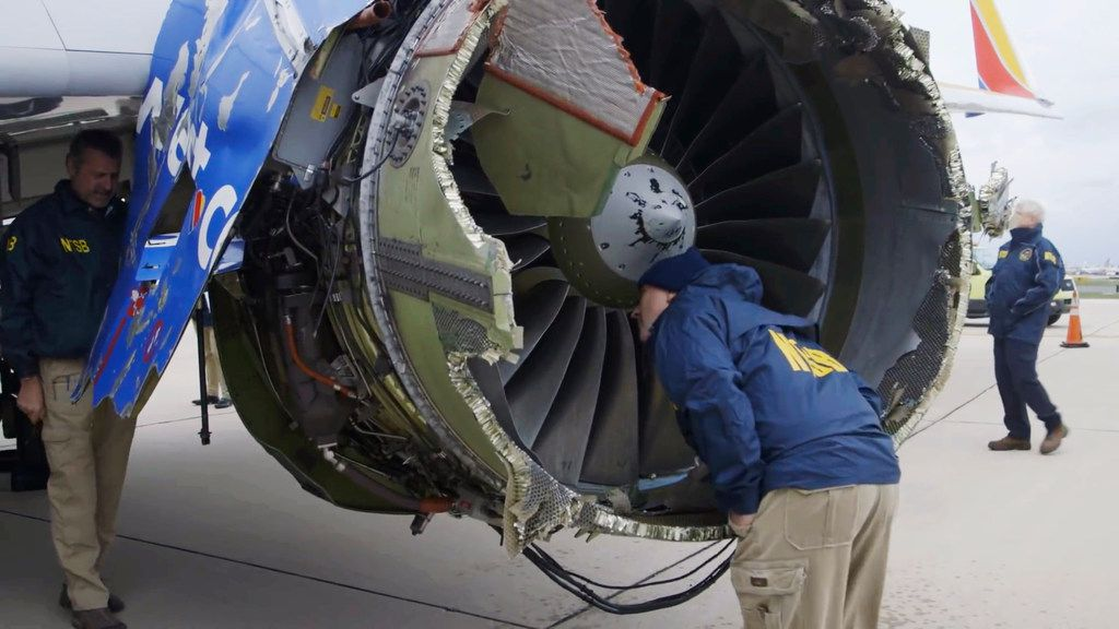 In a video still image provided by the National Transportation Safety Board, investigators in Philadelphia examine the damaged engine that caused the death of a passenger on a Southwest Airlines plane on Tuesday, April 17, 2018. The engine on the plane broke apart shortly after takeoff from La Guardia Airport in New York, killing a woman sitting in a window seat near the blast. (National Transportation Safety Board)