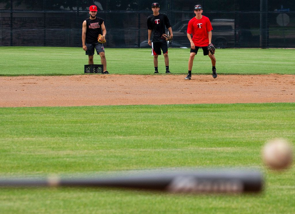 Nike Tratree, Christian Garcia, and Christian Blue watch as coach Will Averitt hits the ball during a baseball practice at Euless Trinity High School in Euless, Texas Wednesday, May 22, 2019. (Shaban Athuman/Staff Photographer)