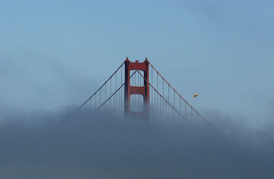 A small plane files past a tower of the Golden Gate Bridge partially covered by fog in San Francisco.
