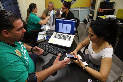 Ulises Hernández (izq.), un agente de seguros en Florida, ayuda a Yuricel Durán a comprar seguro bajo la Ley de Seguro de Salud Asequible.