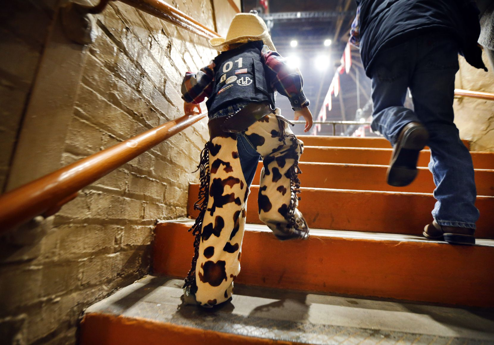 In full rodeo regalia, two-year-old Austin Curtis of Fort Worth climbs the steep steps to the seating bowl of Will Rogers Memorial Coliseum.