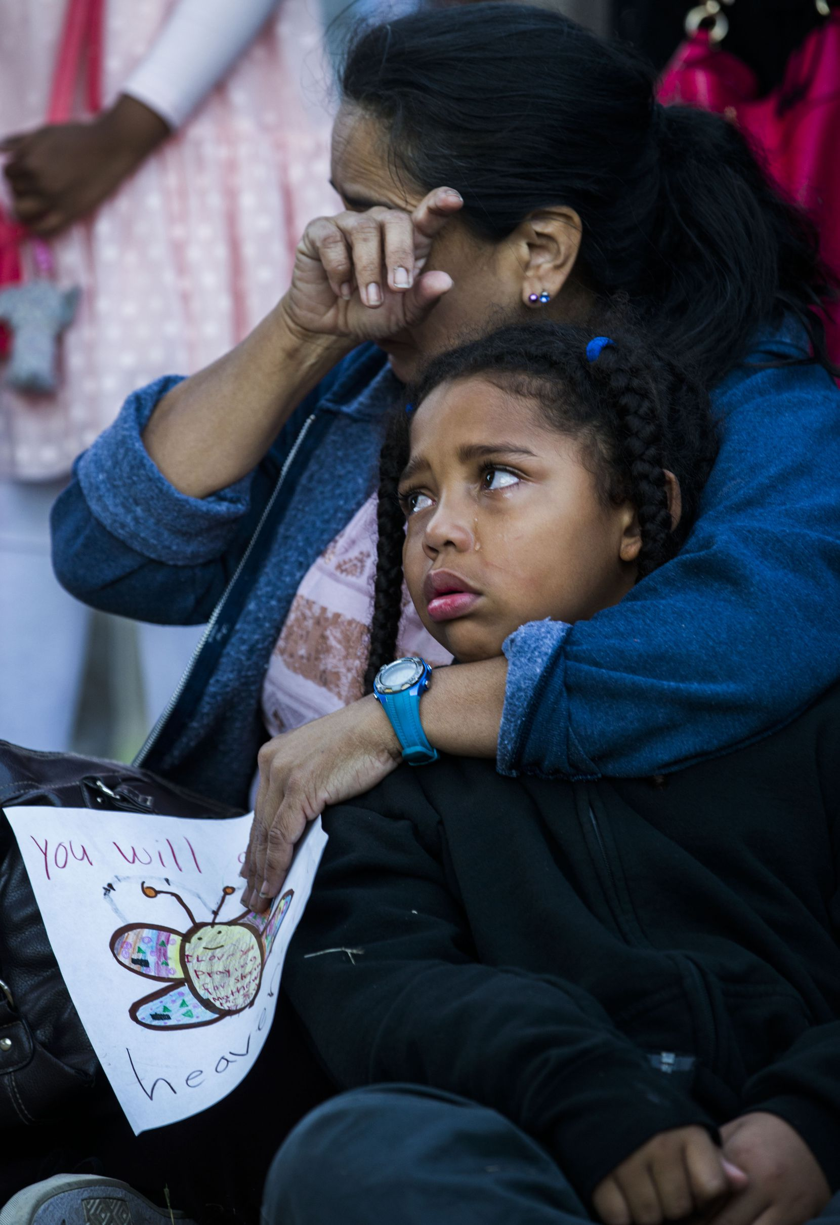 Diana Delgado wipes away a tear as she holds her crying grandson Lejohn Rogers, 7, during a vigil at a memorial Sunday for Sherin Mathews.