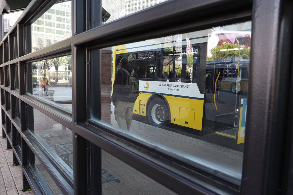 People wait at the DART West Transfer Center for DART buses in downtown Dallas on Friday, March 25, 2016.