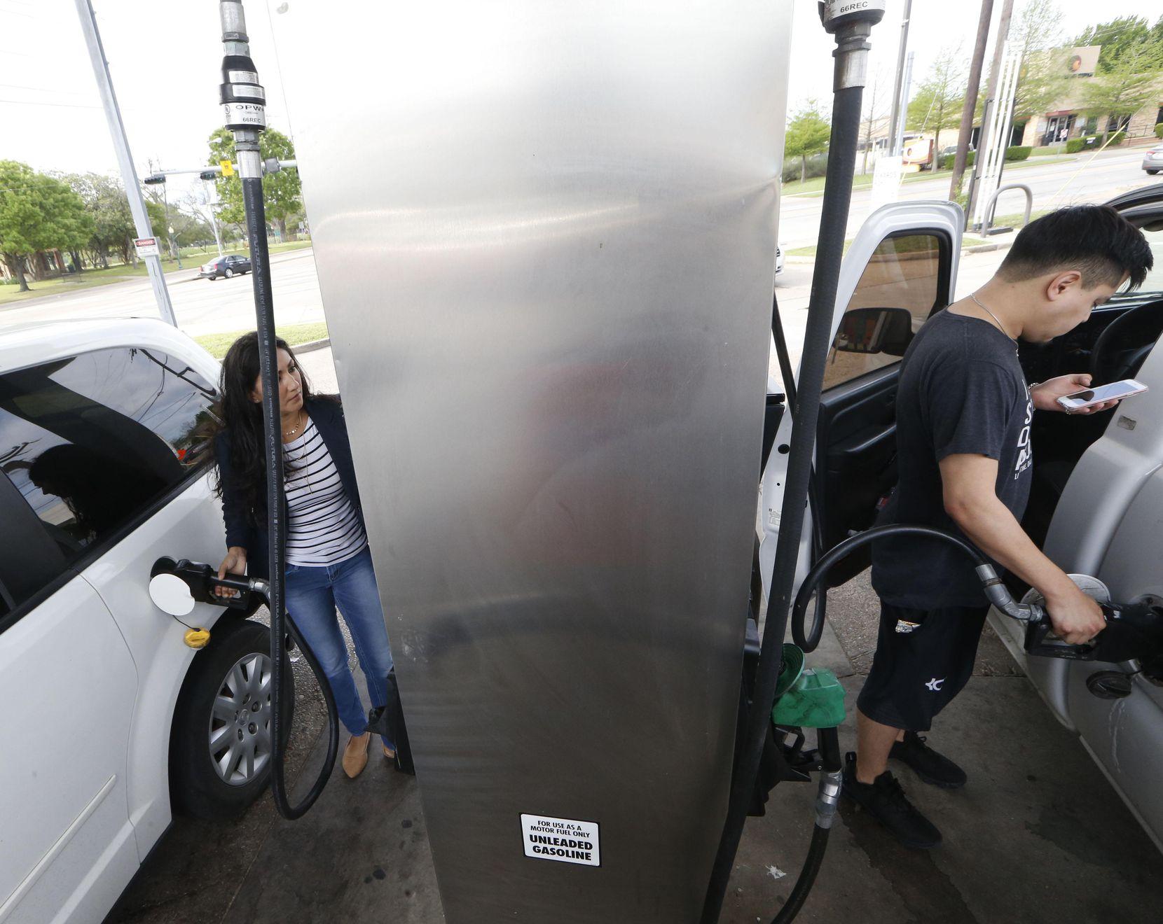 Amelia Banda (izq.) y Andrew Rivas ponen gasolina en una estación en N. Zang Boulevard y Colorado, en Dallas.Los precios de la gasolina están al alza en el Norte de Texas, pero expertos creen que no subirá mucho más. NATHAN HUNSINGER/DMN