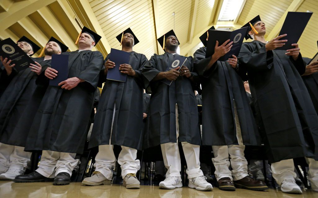 Inmates follow the May 9 commencement program of Southwestern Baptist Theological Seminary at the Texas Department of Criminal Justice's Darrington Unit in Rosharon. Thirty-three convicts graduated with a bachelor's degree in biblical studies. (Jae S. Lee/Staff Photographer)