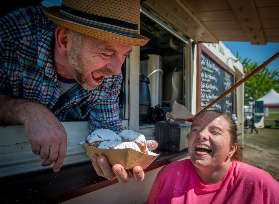 Summer Ladd gets a face full of powdered sugar from trio of beignets served up by proprietor of the Beignet Bus, Toby Tindall, at The Trailhead at Clearfork. Keep an eye out for this bus around town.