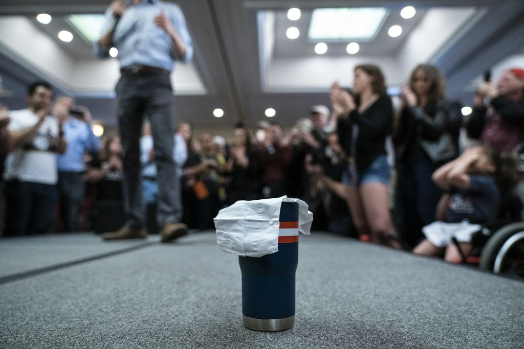 A napkin covers a coffee mug belonging to Beto O'Rourke as he speaks during a town hall in Alexandria, Va.