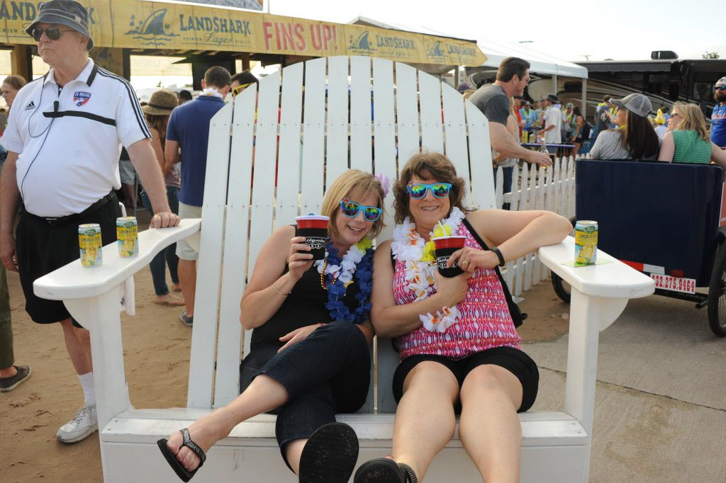 Friends relax in a giant beach chair at the Jimmy Buffett tailgate party at Toyota Stadium in Frisco, TX on May 30, 2015.