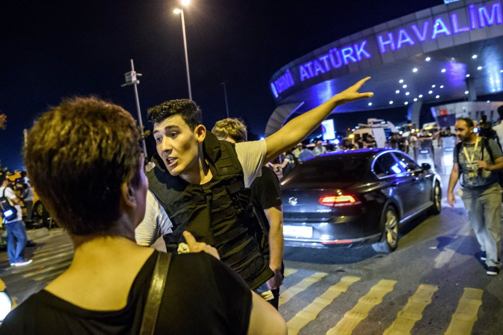 A Turkish police officer directs a passenger at Ataturk airport in Istanbul June 28, 2016 after two explosions followed by gunfire hit Turkey's biggest airport. A