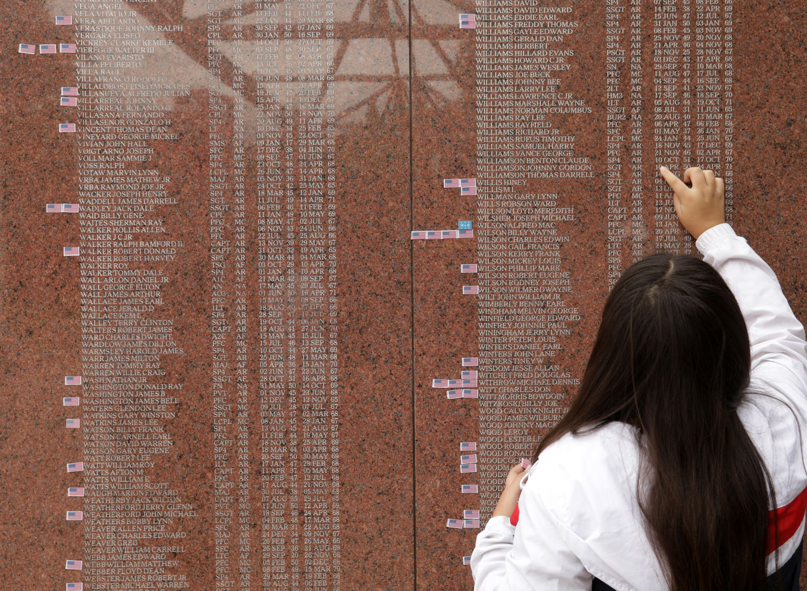 A visitor to the Texas Vietnam Veterans Memorial on Monday scans the names and dates. More than 3,000 names are engraved in the red granite tablets.