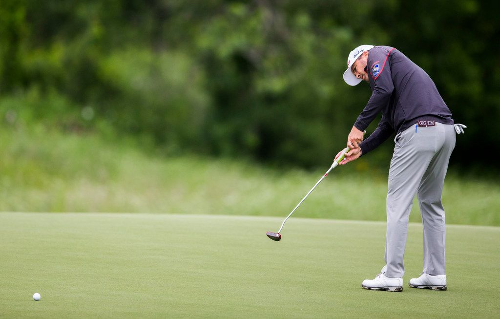 """Ryan Palmer putts on the 15th green during round 2 of the AT&T Byron Nelson golf tournament on Friday, May 9, 2019 at Trinity Forest Golf Club in Dallas. Palmer carries a scorecard holder that says """"Gig Em."""" (Ashley Landis/The Dallas Morning News)"""