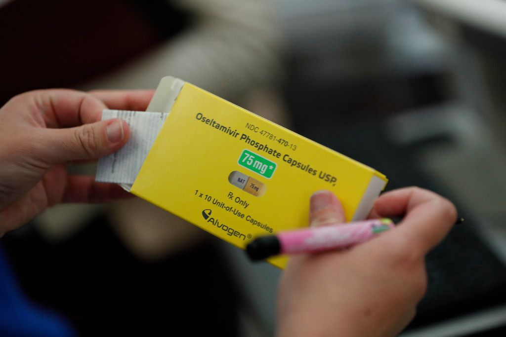 Stephanie Scott, a  nurse in the emergency department at St. Joseph's Hospital in Orange, Calif., holds a box of oseltamivir phosphate, often known by the brand name Tamiflu, which reduces flu symptoms if taken within 48 hours of getting flu symptoms.
