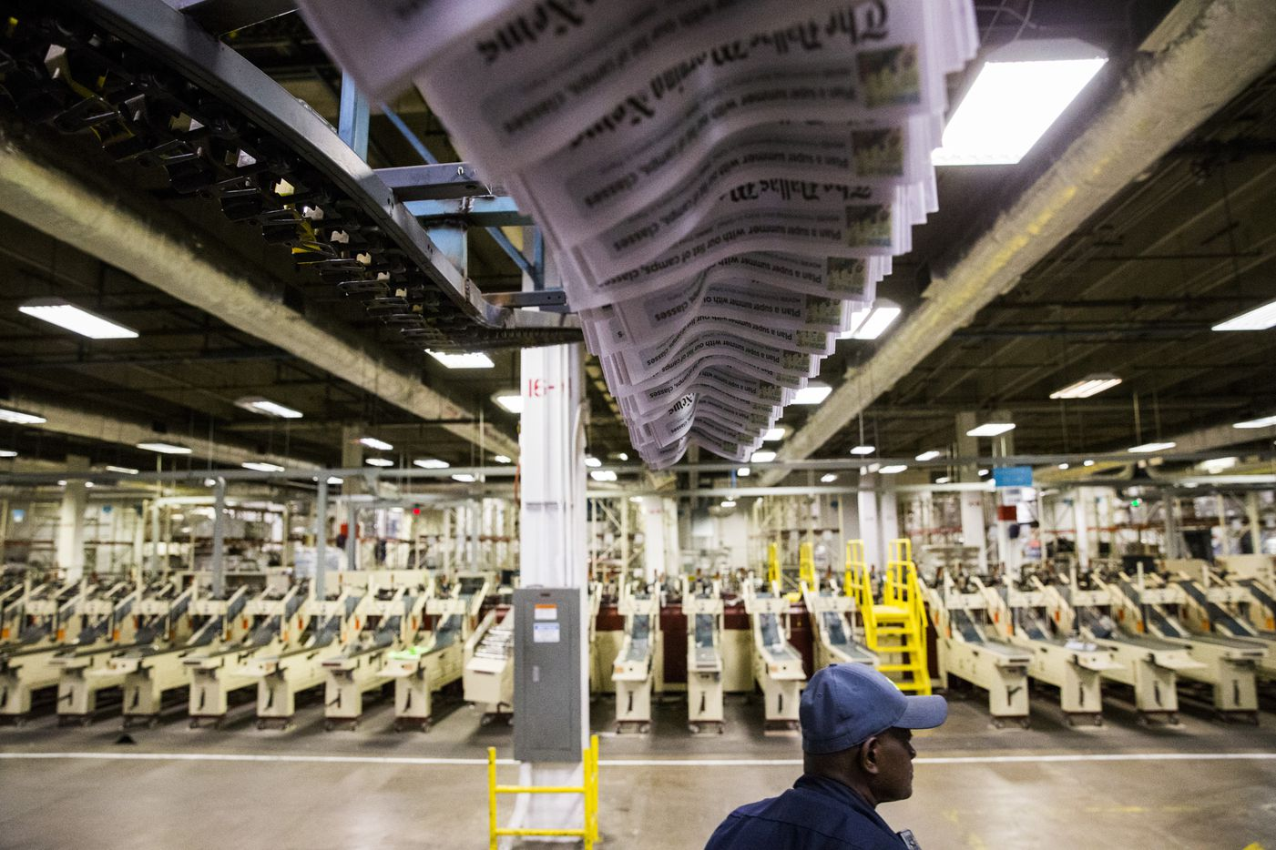 Copies of the Friday, April 7, 2017 issue move overhead. (Ashley Landis/The Dallas Morning News)