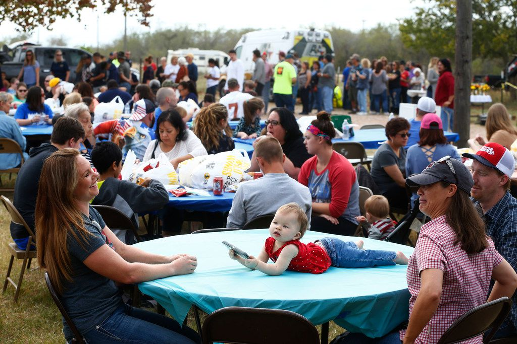 Amy Psencik. (from left) watches as Vivian Wofford, 1, plays with a phone with her parents Heather and Jacob Wofford during Smokin' Angels BBQ Relief in St. Mark's Lutheran Church in Adkins, Texas on Nov. 11, 2017. All proceeds from the event go to the victims of the First Baptist Church in Sutherland Springs, Texas was the site of a shooting that killed 26 parishioners and left 30 injured.