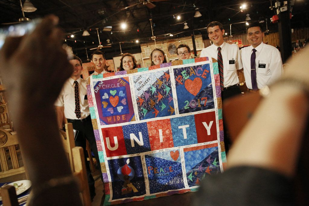 Members of the Church of Jesus Christ of Latter-day Saints take a pictures with a unity quilt designed by Faith Forward Dallas and the Oak Lawn United Methodist Church during the National Day of Prayer Luncheon.