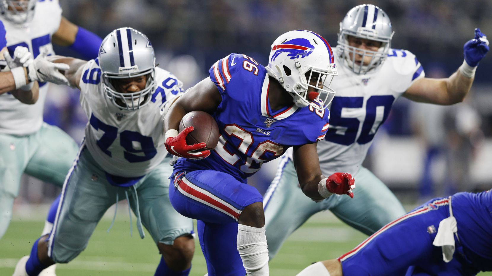 Buffalo Bills running back Devin Singletary (26) runs up the field as Dallas Cowboys defensive end Michael Bennett (79) and Dallas Cowboys outside linebacker Sean Lee (50) close in on him during the second half of play at AT&T Stadium in Arlington, Texas on Thursday, November 28, 2019. The Buffalo Bills defeated the Dallas Cowboys 26-15. (Vernon Bryant/The Dallas Morning News)