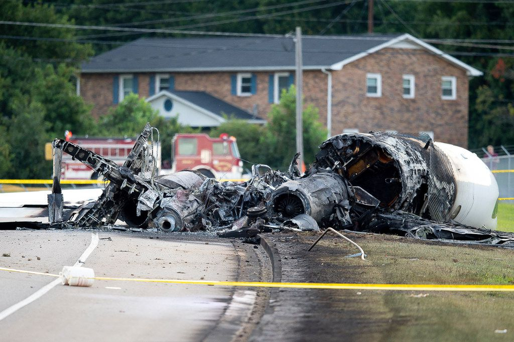 The charred remains of a plane lie along Highway 91 near Elizabethton Municipal Airport in Elizabethton, Tenn., after a crash landing Thursday, Aug. 15, 2019. Dale Earnhardt Jr., his wife and daughter were on board the plane. everyone on board survived. (Calvin Mattheis/Knoxville News Sentinel via AP)