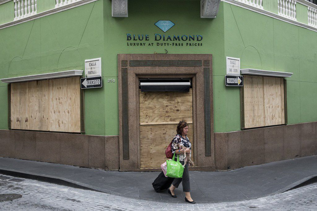 """SAN JUAN, PUERTO RICO - SEPTEMBER 19: A woman passes a boarded up business as residents prepare for a direct hit from Hurricane Maria on September 19, 2017 in San Juan, Puerto Rico. Puerto Rico Gov. Ricardo Rossello is saying Maria could be the """"most catastrophic hurricane to hit"""" the U.S. territory in a century. (Photo by Alex Wroblewski/Getty Images)"""