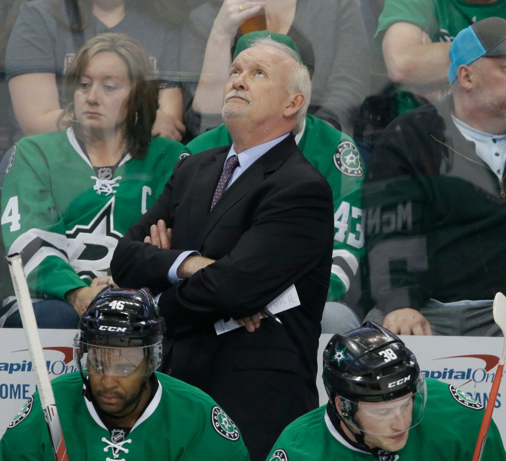Dallas Stars head coach Lindy Ruff looks up at the scoreboard behind center Gemel Smith (46) and center Mark McNeill (38) during the first period of an NHL hockey against the Colorado Avalanche game in Dallas, Saturday, April 8, 2017. (AP Photo/LM Otero)