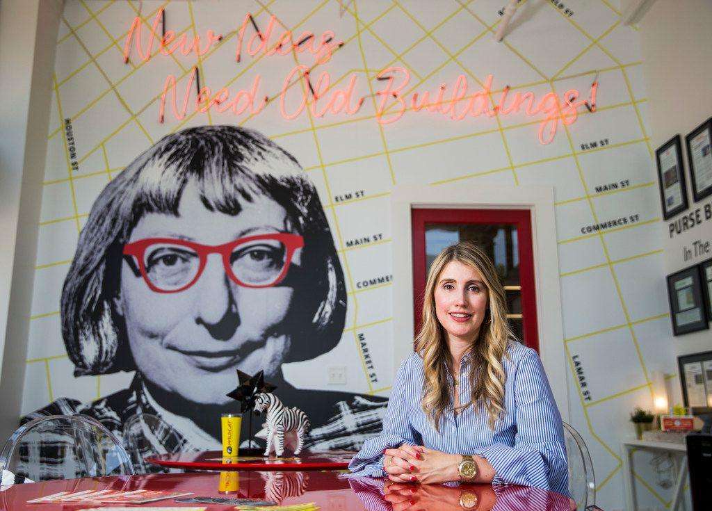 """Tanya Ragan, owner and president of Wildcat Management, at the Purse Building. Prominently featured near the front of the building is a floor-to-ceiling mural of urbanist activist Jane Jacobs and her mantra """"New ideas need old buildings."""""""