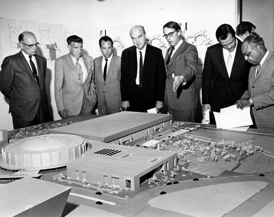 Dallas Mayor J. Erik Jonsson (center, black suit) and architect E. G. Hamilton (gesturing) view a model of the Dallas Convention Center project. To Jonsson's right is council member Wes Wise. Other men are not identified.