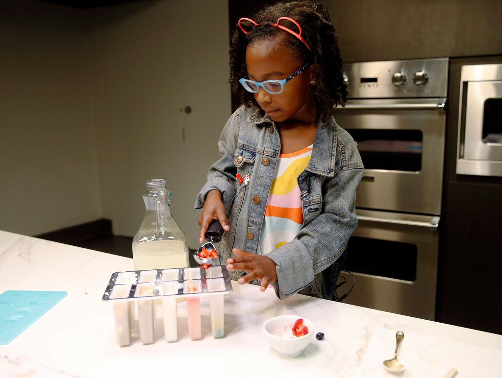 Ellington Young, 7, makes a strawberry and lemonade ice pop.