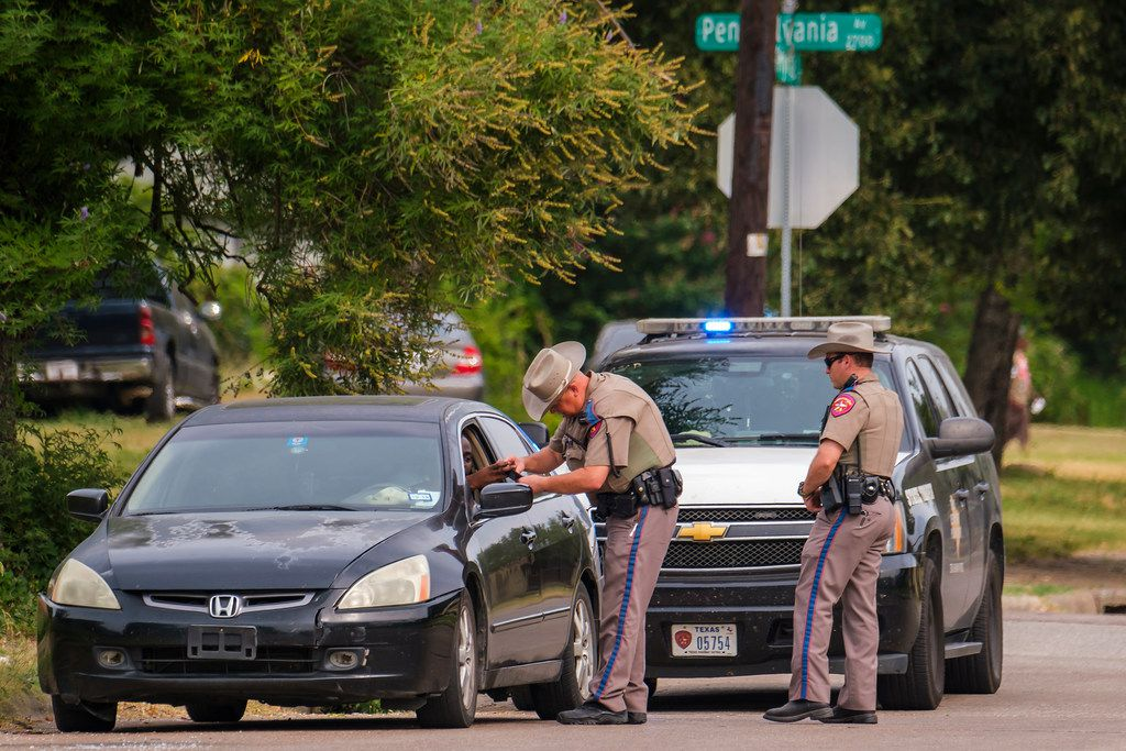 Texas DPS troopers make a traffic stop at Pennsylvania and Myrtle, near the intersection of Malcolm X Boulevard and Martin Luther King Jr. Boulevard, in South Dallas on Thursday.
