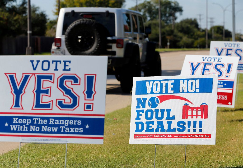 Campaign signs supporting and opposing public assistance for a new Texas Rangers stadium. Voters will decide on the deal Nov. 8. Early voting has already started.