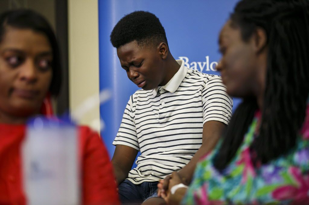 Jermar Taylor, 12, broke down as he recalled the confusion during the July 7 attack Thursday night that killed five police officers and wounded seven more, including his mother, Shetamia Taylor (right). They were at a news conference at Baylor Scott & White Health Center in Dallas.. (Marcus Yam/Los Angeles Times)
