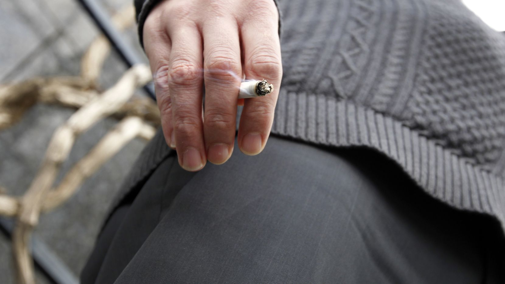 Nathan Morgan smokes a cigarette during a break from work outside the Renaissance Tower in downtown Dallas. (File 2013/The Dallas Morning News )