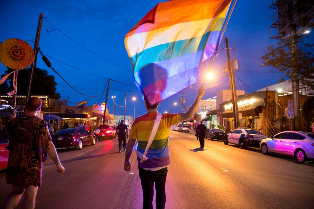Zach Cussins marches with the Rainbow Flag during the Queer Bomb Dallas procession march though Deep Ellum streets on June 25, 2016 in Dallas. (Ting Shen/The Dallas Morning News)