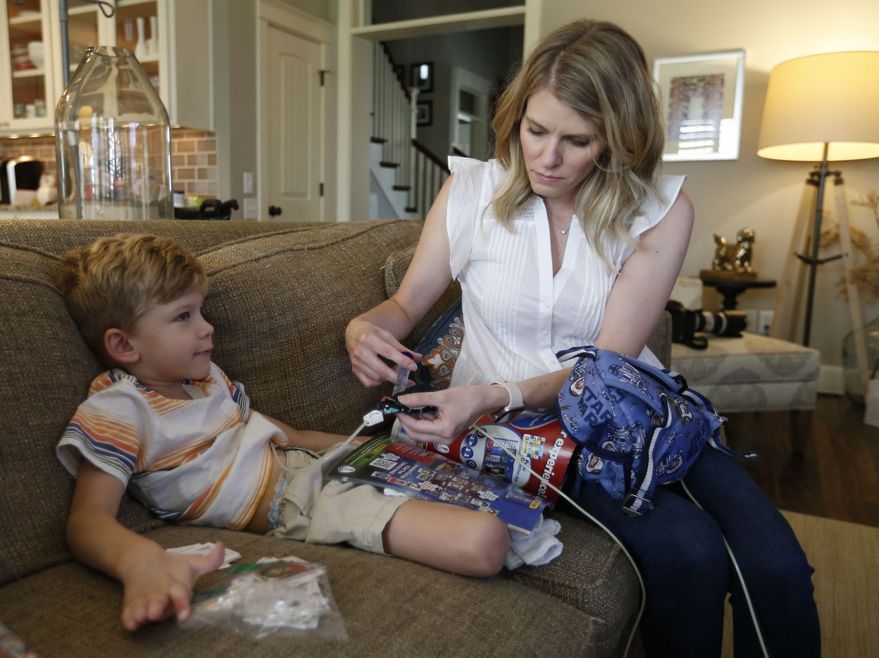 Kasey Woleben, right, injects water into her son Will, who has a rare neurodegenerative disease called Leigh Syndrome, at their home in McKinney, Texas, Wednesday, June 20, 2018.