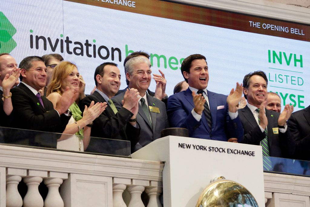 Invitation Homes President & CEO John Bartling Jr., fourth left, is applauded as he rings the New York Stock Exchange opening bell, Wednesday, Feb. 1, 2017, to mark his company's IPO. (AP Photo/Richard Drew)