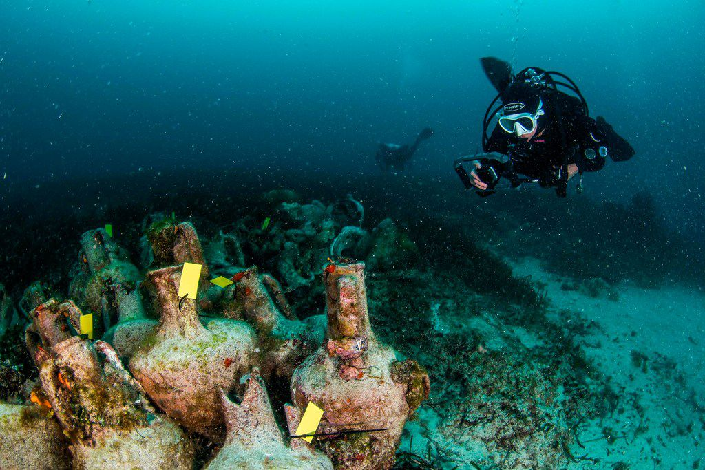 Divers explore the ruins of the ancient Greek shipwreck near the Aegean island of Alonissos, Greece.