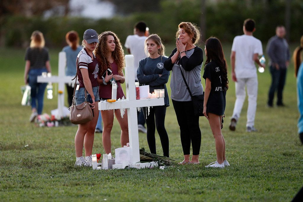 People pay homage at the memorial crosses for the 17 deceased students and faculty from the Wednesday shooting at Marjory Stoneman Douglas High School, in Parkland, Fla., Friday, Feb. 16, 2018. Nikolas Cruz, a former student, was charged with 17 counts of premeditated murder on Thursday.