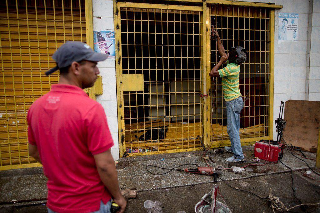 Un dueño de una tienda repara la puerta de seguridad de la entrada de su supermercado saqueado por manifestantes la noche anterior, en Ciudad Bolivar, Venezuela, el lunes 19 de diciembre 2016. (AP)