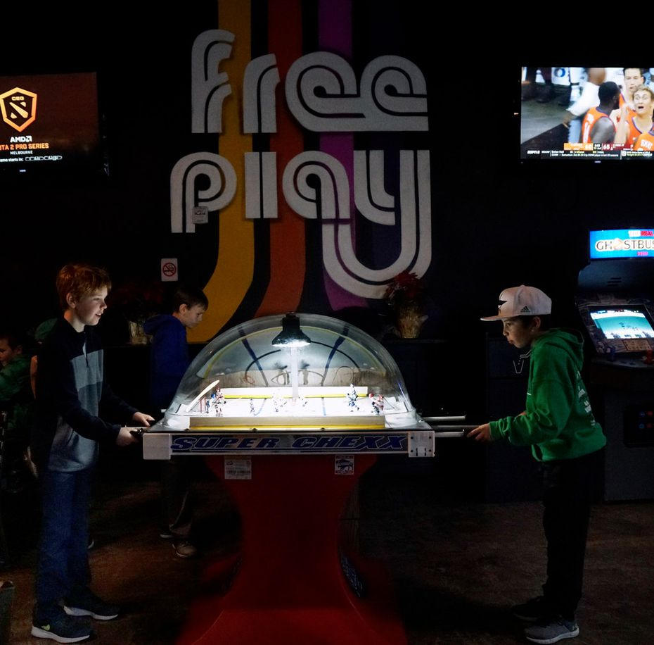 Zackery Verner (9) and Oliver Bench (10) play bubble hockey at Free Play in Arlington.