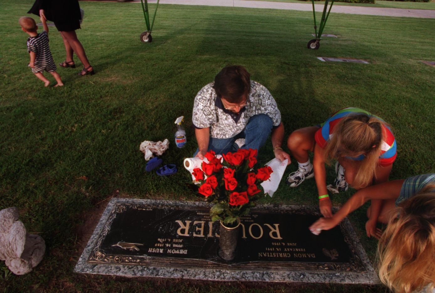 Darin Routier cleans the gravestone of his two slain sons, Devon and Damon, at Rest Haven Cemetary in Rockwall in June 1997.