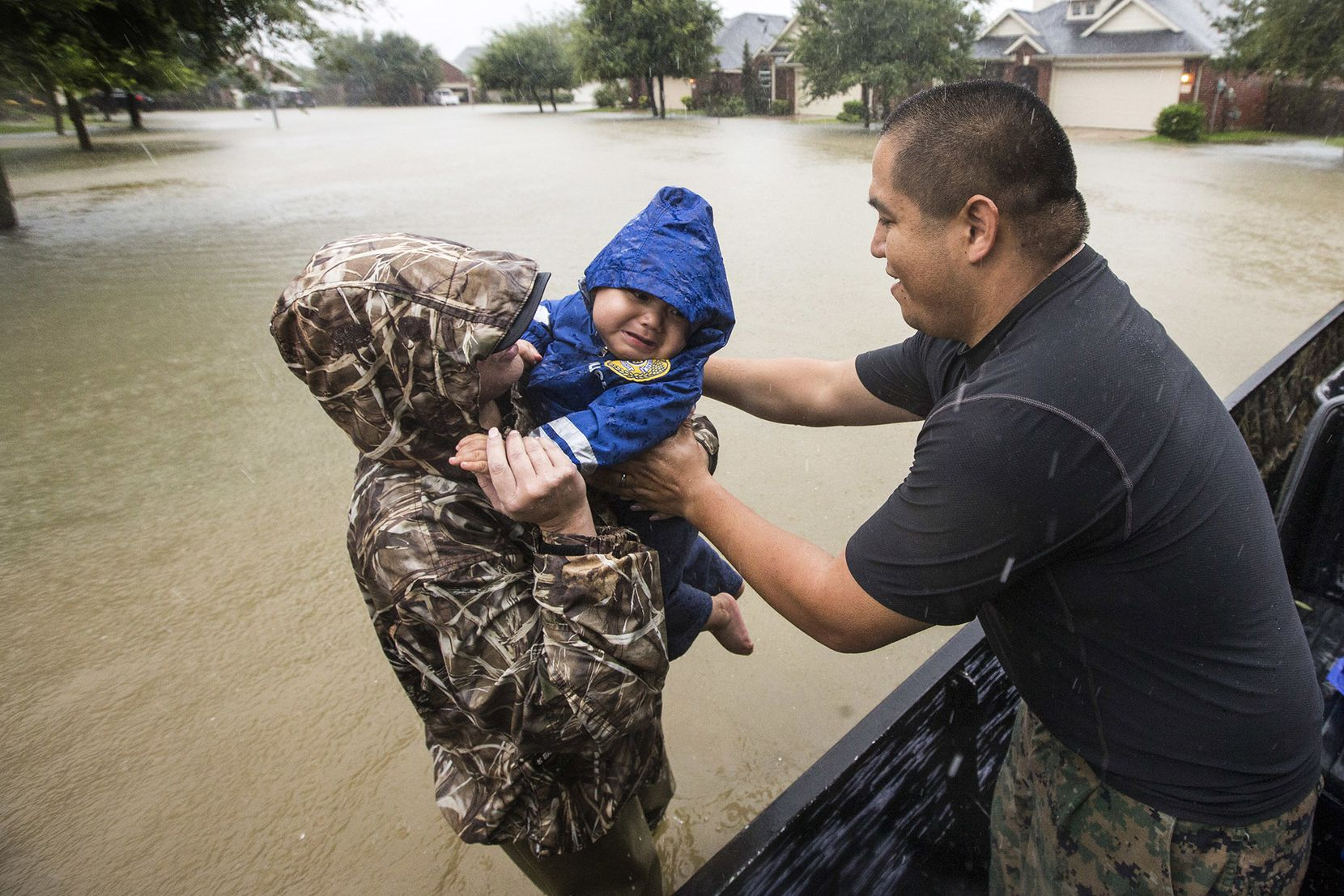Wilfredo Linares reaches out for his baby, Mason, as they are evacuated from Grand Mission subdivision, as the water rises from heavy rains from Tropical Storm Harvey on Monday, Aug. 28, 2017, in Fort Bend County, Texas. (Brett Coomer/Houston Chronicle via AP)