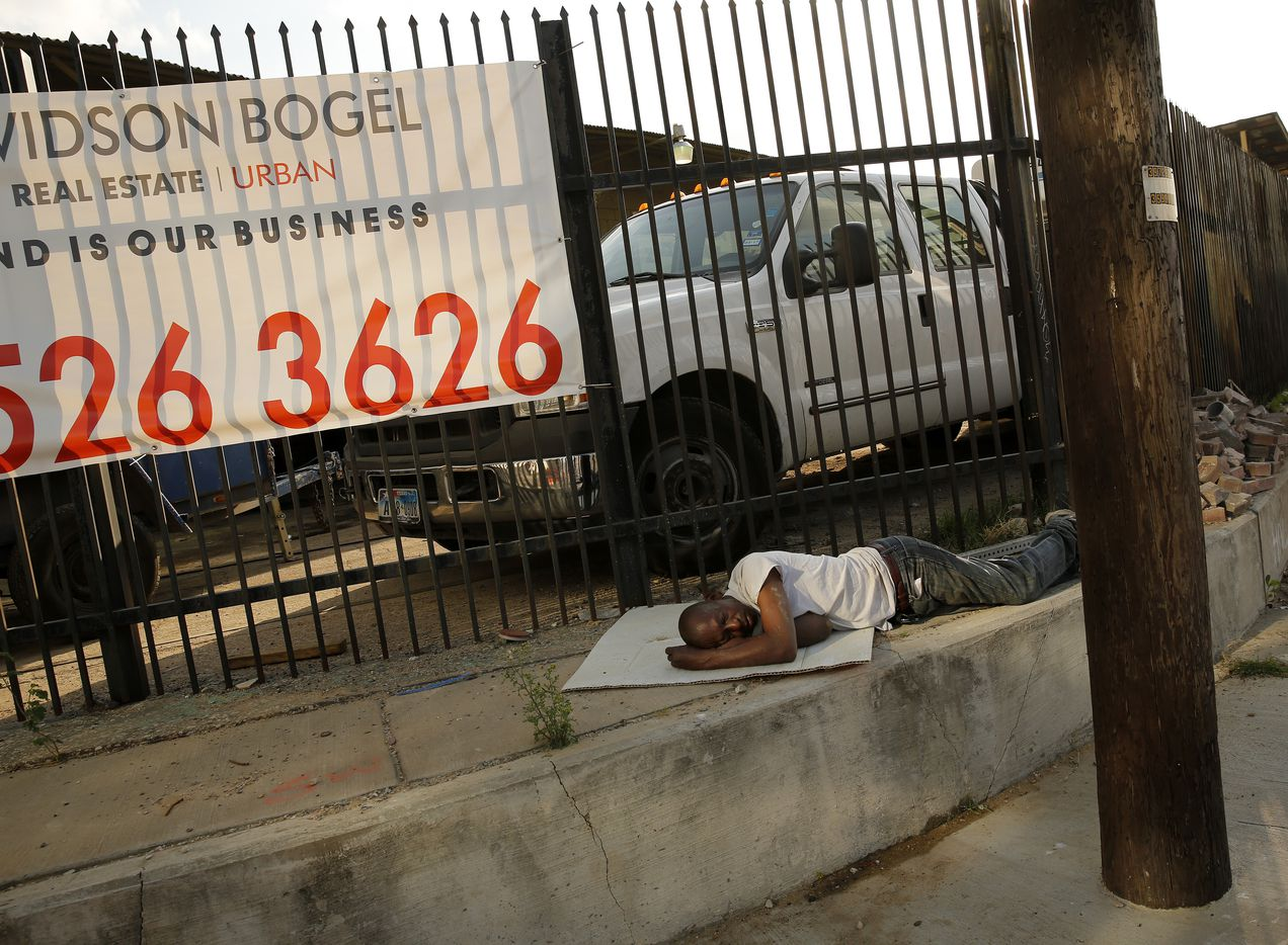 A man sleeps on a piece of cardboard along Singleton Blvd across the street from Trinity Groves near the Margaret Hunt Hill Bridge in West Dallas, Wednesday, March 22, 2017. (Tom Fox/The Dallas Morning News)