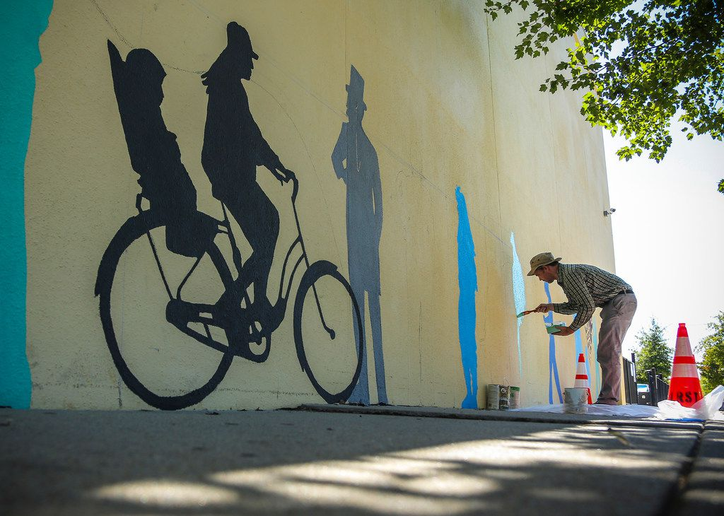 John Kushmaul paints silhouette figures along a wall on South Main Street between 12th and 13th streets in downtown Little Rock, Ark. The figures are part of a 100-by-22-foot mural that will serve as a gateway mural to the SOMA district.