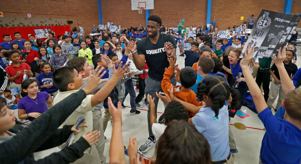 Mavericks guard Wesley Matthews gets high-fives from kids he makes a special appearance in support of a peanut butter and jelly food drive event at Florence Elementary School in Mesquite.