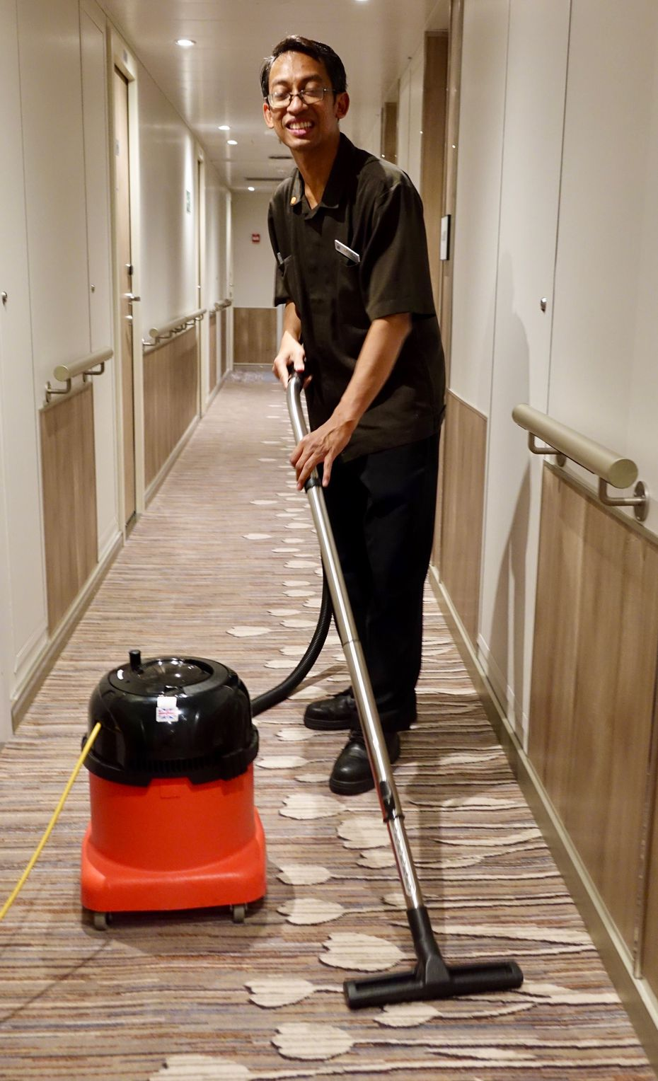 Cabin steward Budhi Prasetyo vacuums the hallway daily after he and his partner have made up 29 cabins aboard the Nieuw Statendam.