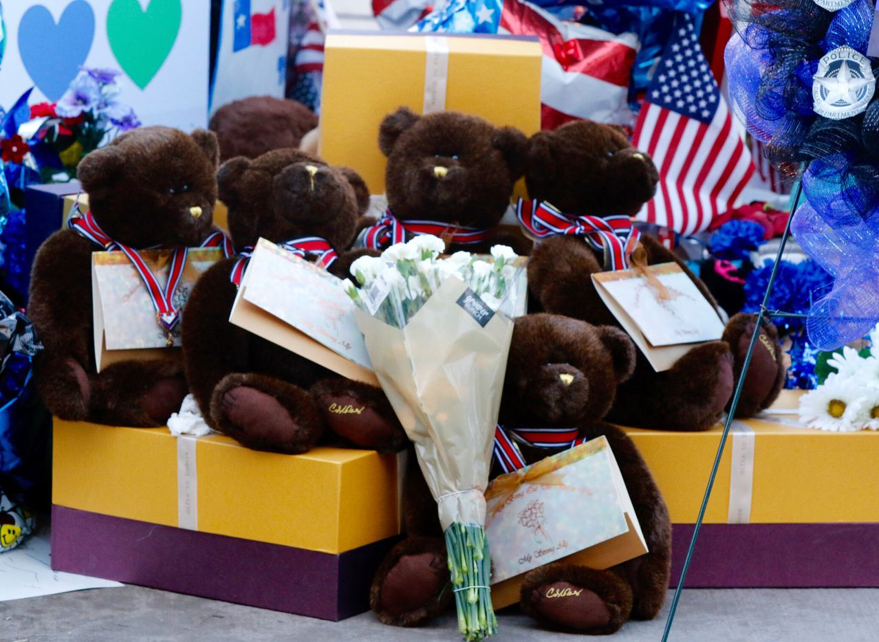 Five teddy bears in honor of the fallen officers are part of the memorial at Dallas police headquarters on Monday, July 18, 2016.