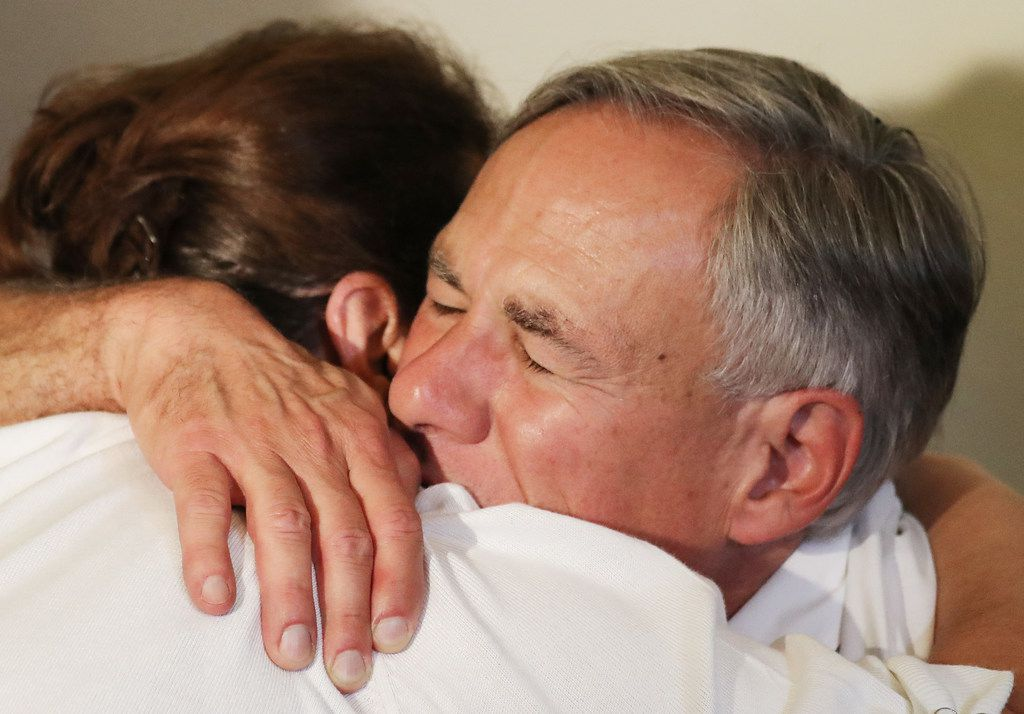 Texas Gov. Greg Abbott  hugs a woman following a vigil for victims at St Pius X Church after a mass shooting which left at least 20 people dead on Aug. 3 in El Paso,